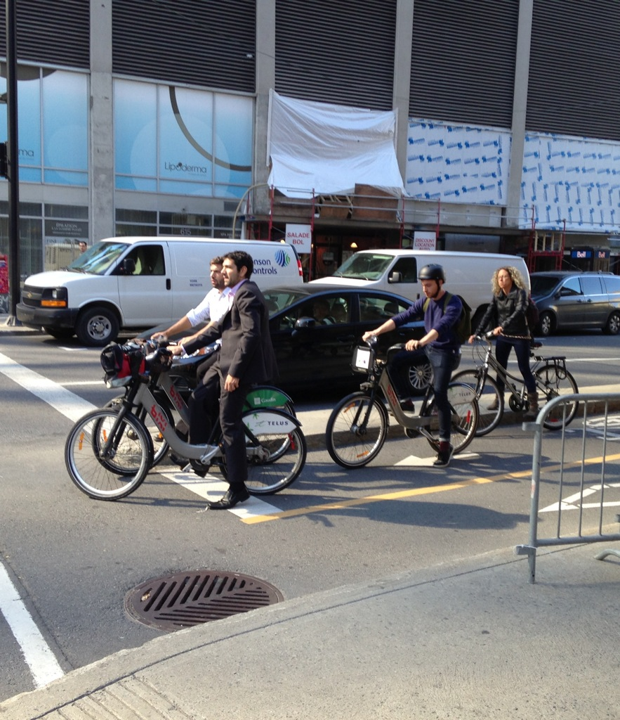 These Bixi riders and cyclists at lunch in Montreal. Only one of them is wearing a helmet.
